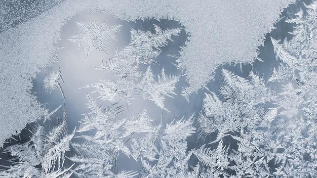 Os padrões únicos de gelo no vidro da janela. criatividade de natureza sazonal