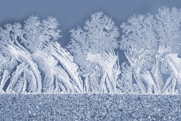 Os padrões únicos de gelo no vidro da janela. fundo natural e textura
