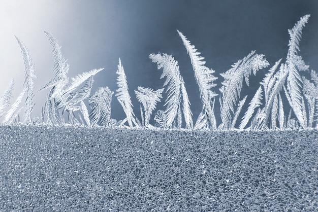 Os padrões únicos de gelo no vidro da janela. texturas naturais e fundos
