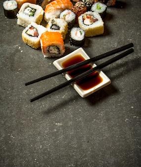 Os pãezinhos e o sushi com molho de soja. na mesa de pedra.
