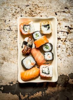 Os pãezinhos e sushi, frutos do mar no prato em fundo rústico