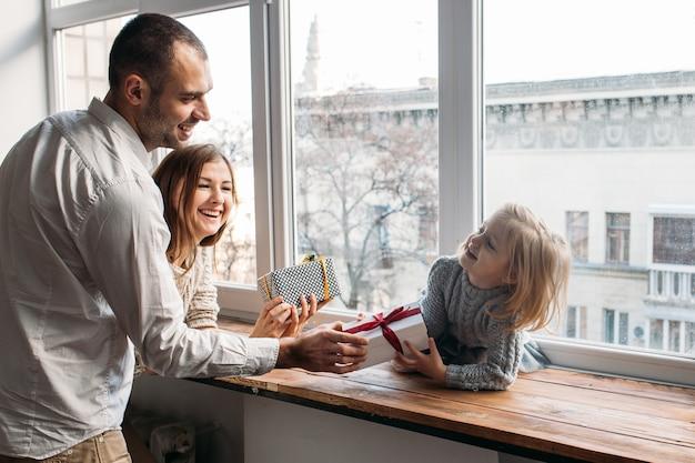 Os pais apresentam a caixa de presente para a filha em casa, perto da janela