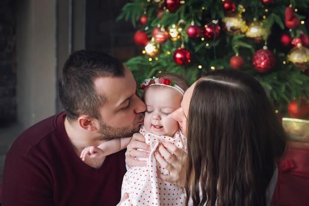 Os pais beijam sua filha na árvore de natal.