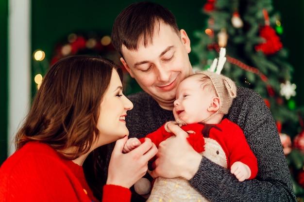 Os pais brincam com a pequena filha no chapéu dos veados segurando-a nos braços e de pé diante de uma árvore de natal