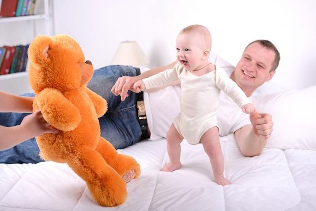 Os pais brincam com o bebê recém-nascido em casa.