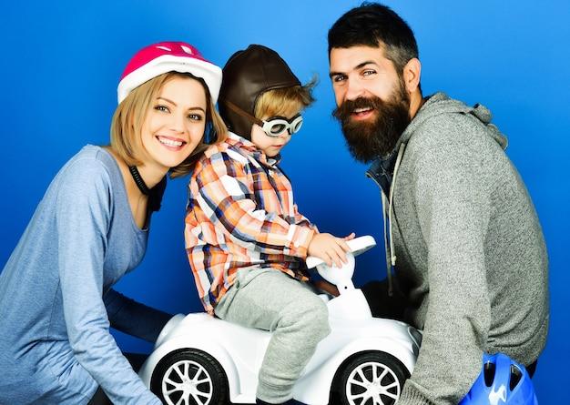 Os pais brincam com o filho no carro de brinquedo. família feliz em proteger os capacetes desportivos.