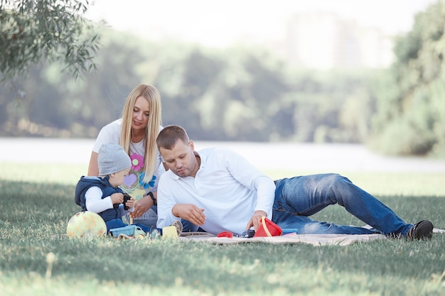Os pais brincam com o filho pequeno sentado na grama do parque