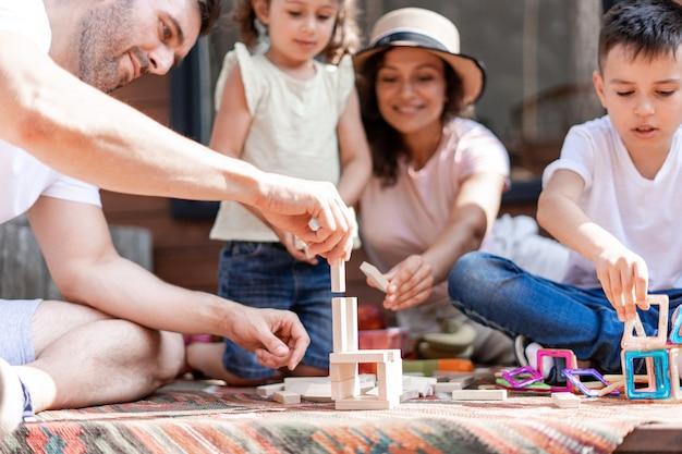 Os pais brincam com os filhos em jogos educativos na rua durante o fim de semana de verão, uma família de quatro, dois filhos e pais