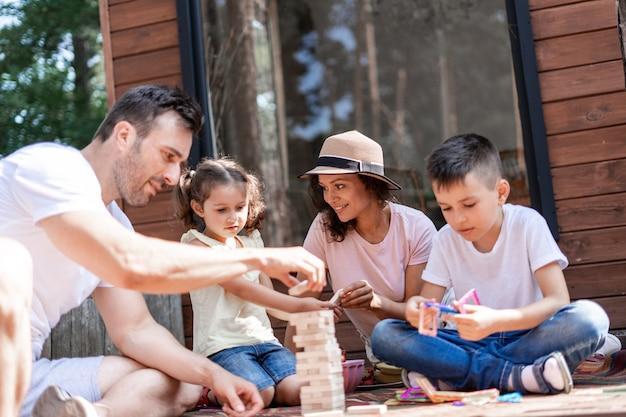 Os pais brincam com seus filhos, se divertindo brincando em jenga, durante as férias de verão perfeitas fora da cidade. a mãe se comunica com a filha enquanto brinca