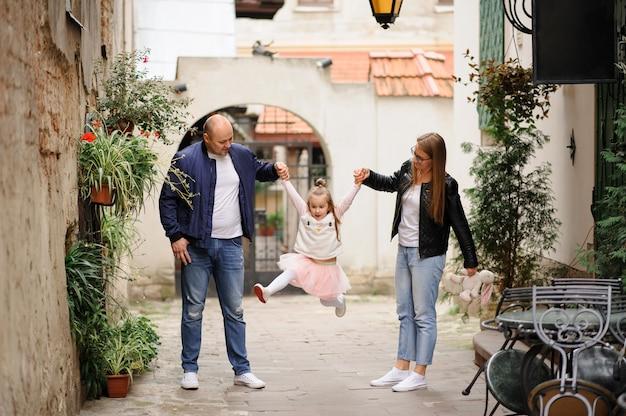 Os pais criaram e seguram a filha pelas mãos. garota se divertindo e agitando as pernas.