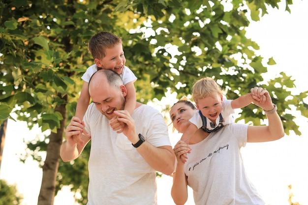 Os pais divertem seus filhos e os montam nos ombros