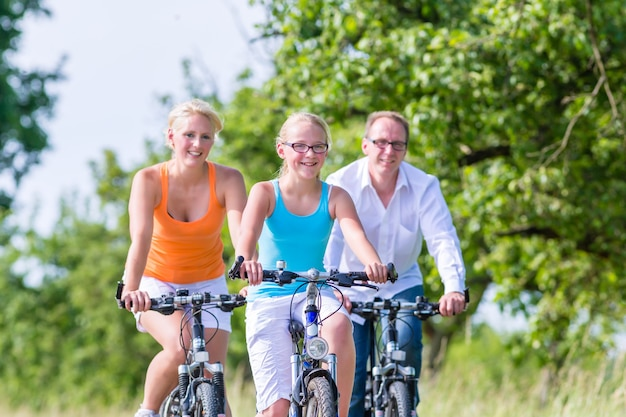 Os pais e a filha fazem um passeio de bicicleta ou de bicicleta na estrada rural