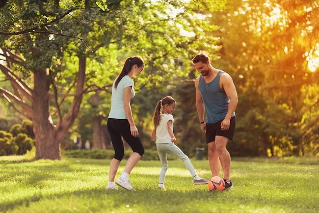 Os pais e a filha jogam futebol.