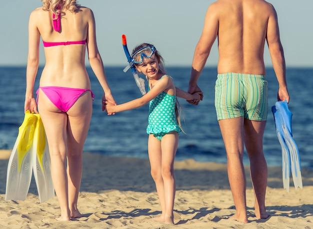 Os pais e sua filha de mãos dadas.