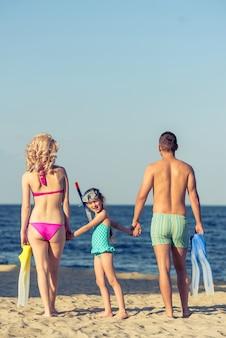 Os pais e sua filha em trajes de banho de mãos dadas.