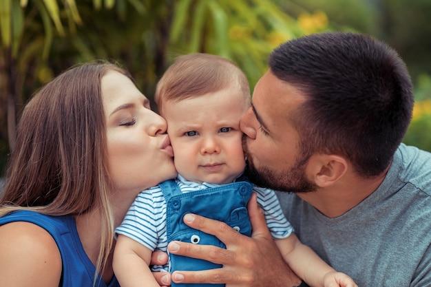 Os pais estão beijando seu filho e o abraçando