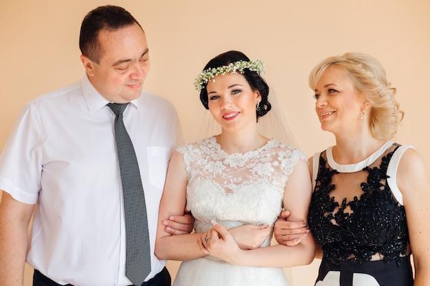 Os pais estão olhando para sua filha em um vestido de noiva olhando para a câmera