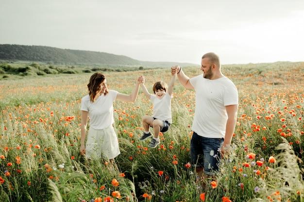 Os pais estão segurando o filho pelas mãos entre o campo de papoulas