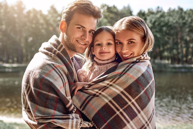 Os pais estão segurando sua filha, eles estão cobertos com um cobertor. foto de close-up