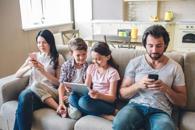 Os pais estão sentados no sofá com os filhos e olham para os telefones. os filhos estão entre mulher e homem. menina tem tablet nas mãos dela. eles olham para a tela.