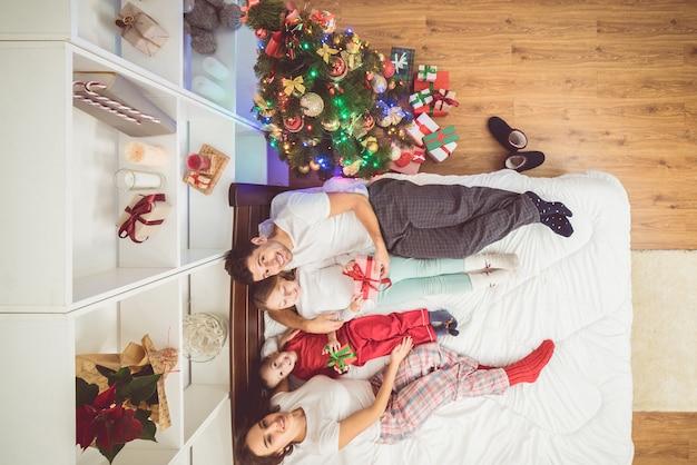 Os pais felizes dando presentes para as crianças perto de uma árvore de natal. vista de cima