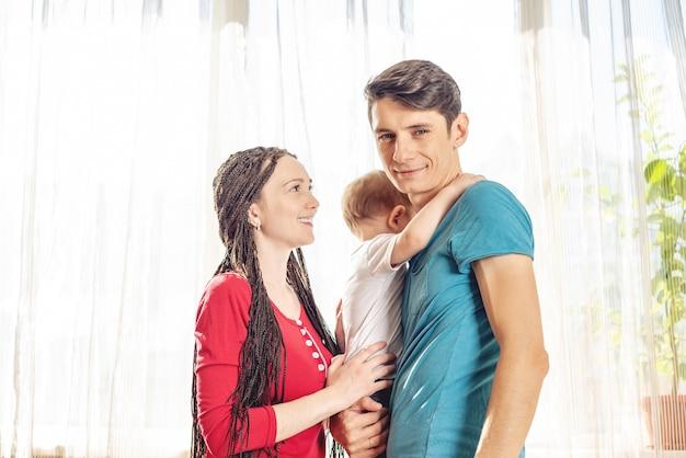 Os pais felizes pai e mãe que jogam com o filho do bebê na manhã. família jovem alegre