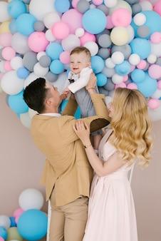 Os pais jovens bonitos sorriem com seu filho de um ano em fundo rosa e azul balões. olhar de família. feliz aniversário
