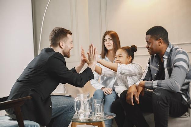 Os pais jovens tiveram problemas em seu relacionamento. o psicoterapeuta resolveu o problema e bateu palmas com a garota.