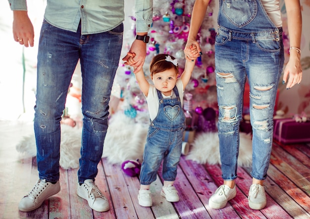 Os pais mantêm as mãos da filha de pé na sala com a árvore chirstmas