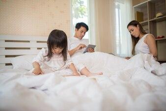 Os pais não se importam com seus filhos e a criança toca o telefone o tempo todo.