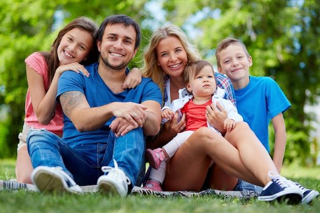Os pais que apreciam com suas crianças no parque
