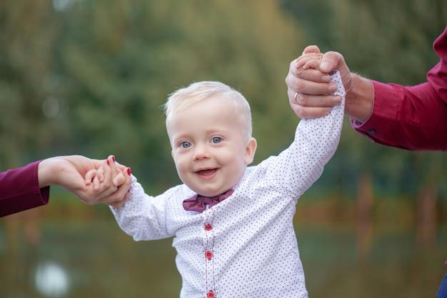 Os pais seguram as mãos do bebê. conceito de família feliz