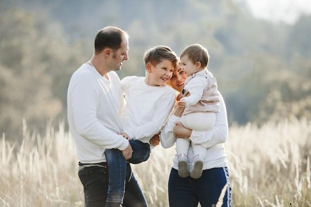 Os pais seguram o filho e a filha e se divertem no campo de trigo
