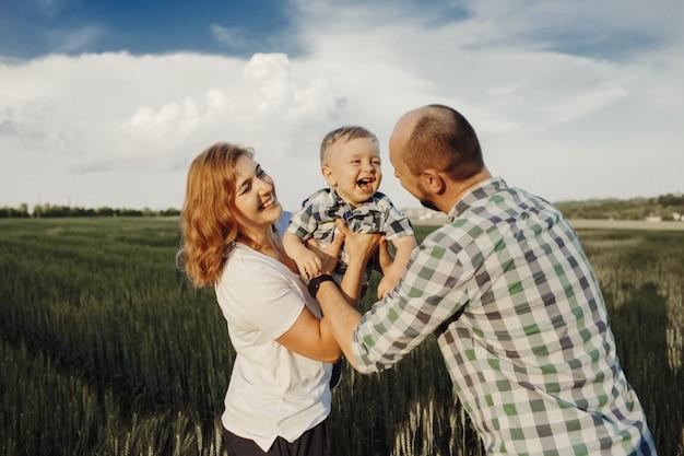 Os pais seguram o filho pequeno e parecem muito felizes