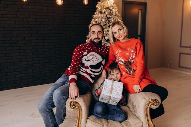 Os pais sentam-se em torno de um menino na cadeira macia antes de uma árvore de natal