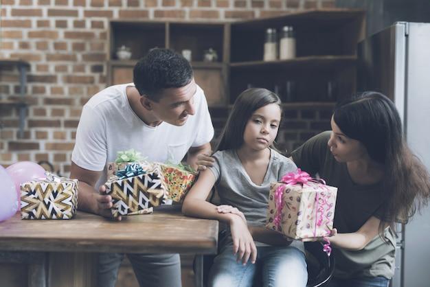 Os pais sorriem para a moça e tentam dar presentes para ela