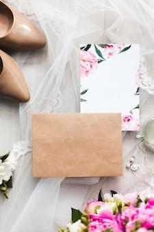 Os papéis de cartões de convite de casamento deitado na mesa decoram com flores, voile, salto alto e uma garrafa de água de toalete.