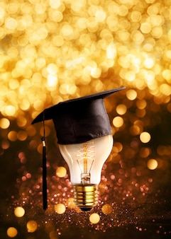 Os parabéns graduados tampam em um bulbo de lâmpada com fundo do grunge das luzes do brilho.
