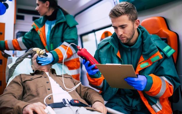Os paramédicos estão trabalhando com um paciente idoso enquanto ele está deitado em uma maca em uma ambulância.