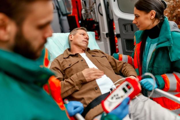 Os paramédicos verificam o nível de oxigênio no sangue e transportam a maca do paciente idoso da ambulância moderna para cuidados médicos adicionais na clínica.