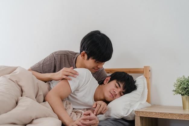 Os pares alegres asiáticos beijam e abraçam na cama em casa. jovens asiáticos lgbtq homens felizes relaxam descansar juntos passam tempo romântico depois de acordar no quarto em casa de manhã.