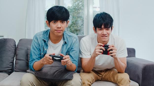 Os pares alegres asiáticos novos jogam jogos em casa, homens lgbtq coreanos adolescentes que usam o manche que tem o momento feliz engraçado junto no sofá na sala de visitas em casa.