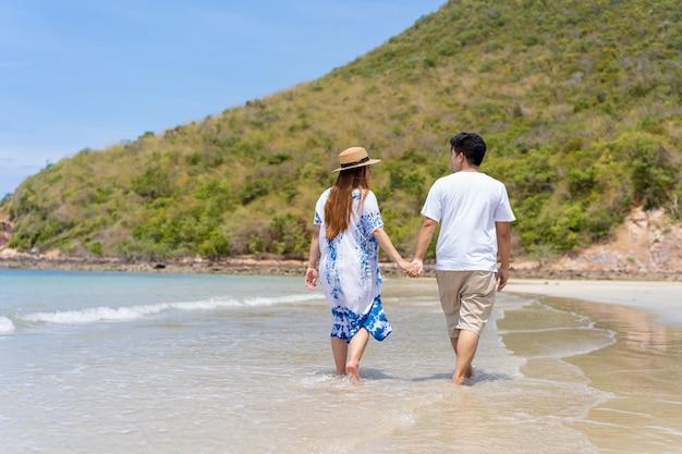 Os pares asiáticos apreciam caminhar junto a praia, conceito de família feliz e felicidade, mulher gravida que anda com seu hasband ao longo da praia.
