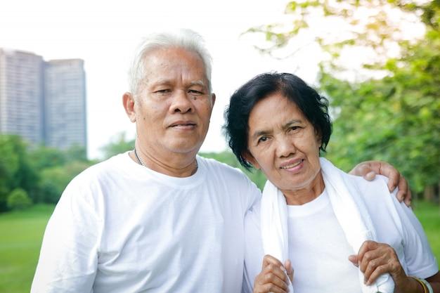 Os pares asiáticos mais velhos exercitam-se no parque.
