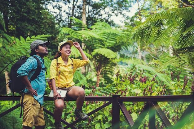 Os pares asiáticos viajam a natureza que relaxa e estuda a natureza nos fores.