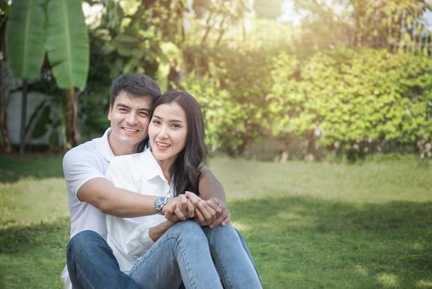 Os pares bonitos têm um bom tempo junto no jardim da frente, o homem e a mulher asiáticos novos abraçam a cabeça do toque principal com cara feliz e sorriem com fundo verde da árvore ao ar livre com espaço da cópia.