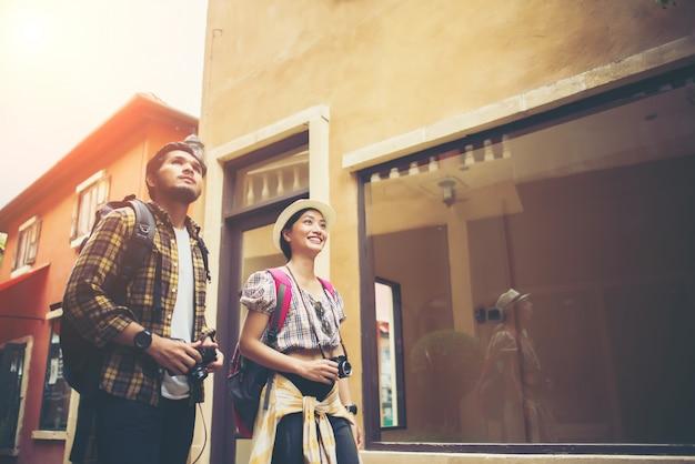 Os pares de turistas novos que andam em urbano apreciam o feriado junto. conceito de viagem do casal.