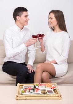 Os pares estão sentando-se junto, comendo o sushi e bebendo o vinho.