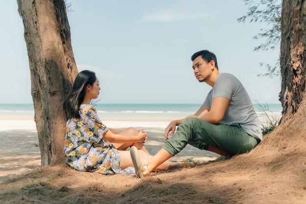 Os pares estão sentando-se junto na praia sob o pinho da árvore.
