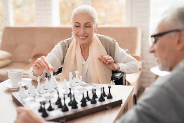 Os pares felizes maduros nas cadeiras de rodas jogam a xadrez.